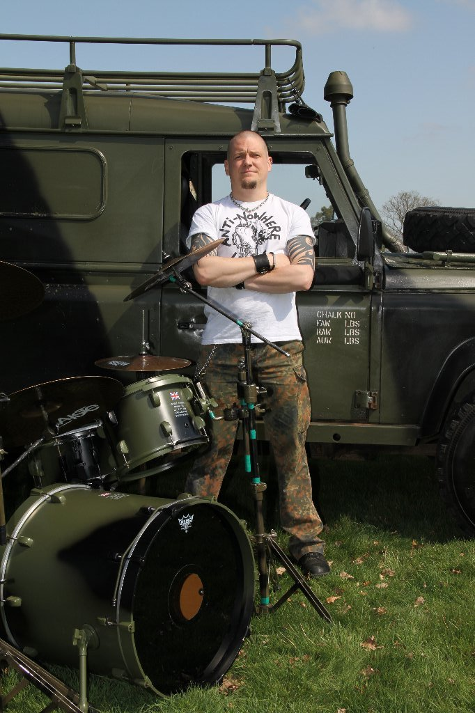 Anti No-Where League drummer with custom drums and matching Land Rover
